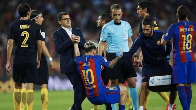 El momento en el que Leo Messi es ayudado a salir del campo de juego. EFE