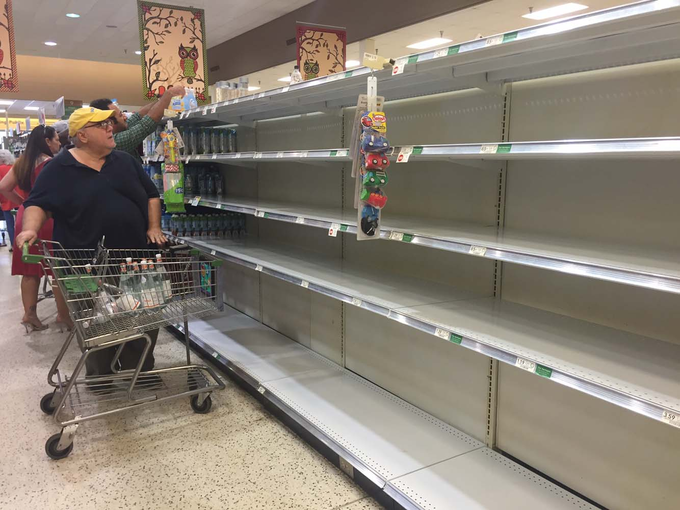 Shoppers pass by empty shelves as they buy supplies ahead of the arrival of hurricane Matthew in Daytona Beach, on October 5, 2016. Weakened but still dangerous, Hurricane Matthew churned toward the Bahamas en route to an already jittery Florida after killing at least nine people in the Caribbean in a maelstrom of wind, mud and water. / AFP PHOTO / Leila MACOR