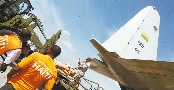 Miembros de la protección civil de Haití observan la descarga de ayuda humanitaria enviada por Bolivia