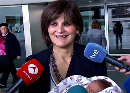 En esta imagen captada de la televisión el martes 18 de octubre de 2016 se ve a Lina Álvarez saliendo del Hospital Lucus Augusti, en la ciudad de Lugo, España, con su hija recién nacida en brazos. La mujer de 62 años dio a luz a una bebé sana y animó a otras mujeres en edad avanzada a hacer lo mismo que ella si es que lo desean. (Atlas TV vía AP)