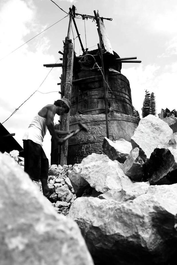 Seorang pembuat kapur di daerah Antang, Kamis (19/6), memecah kerasnya bongkahan batu sebagai bahan mentah sebelum dileburkan jadi kapur. (ash)