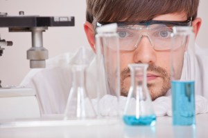 thinking male chemical researcher with manycolourful flasks in a lab