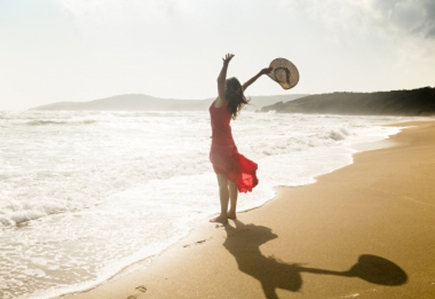 16117144 - happy young woman raises her arms towards the sea