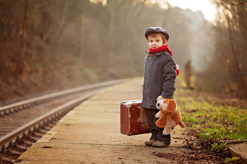 32221471 - portrait of a little boy with s suitcase and a teddy dog, waiting on a railway station