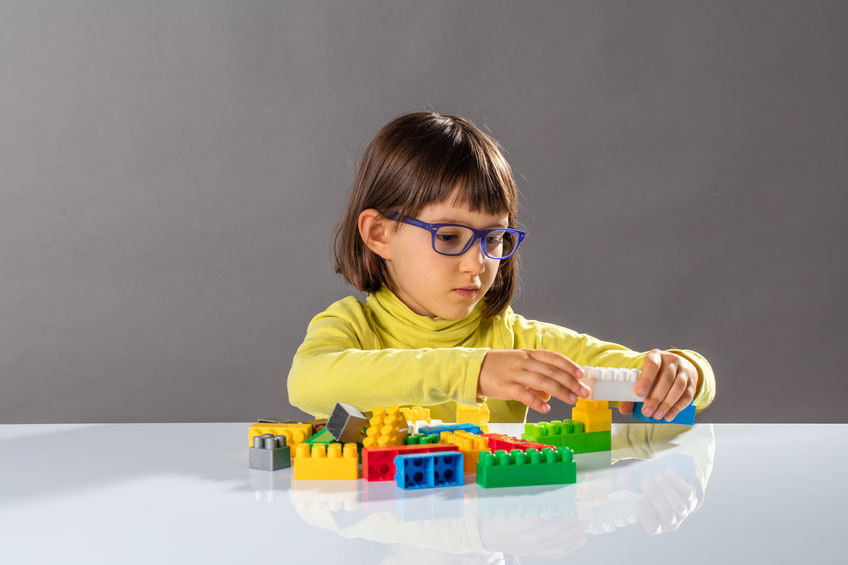 little girl with eyeglasses playing with building blocks, learning to structure, thinking about organizing toys with design, indoors