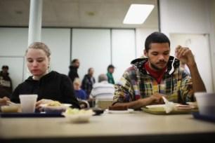 Varias personas toman alimentos en el comedor comunitario de la Iglesia Metodista de Central Park, de Reading, Pennsylvania, al que asisten miles de residentes necesitados de esta localidad que ha sido considerada como la más pobre de los EEUU. De sus 90 mil habitantes, unos 65 mil viven por debajo del índice de pobreza según cifras oficiales. Spencer Platt/Getty Images