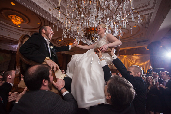 bride and groom hoisted up in chairs at wedding reception - photo: Daniel Fugaciu Photography | via http://emmalinebride.com