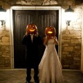 bride and groom holding pumpkins in front of faces halloween wedding