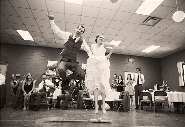 bride and groom jumping the broom at wedding photographed by third line studios