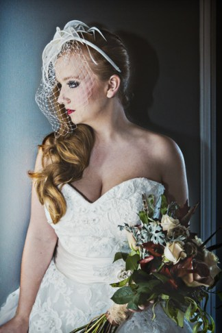 brides birdcage veil fascinator and sweetheart neckline gown