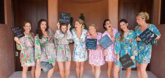 bridesmaids with chalkboards describing how they met the bride