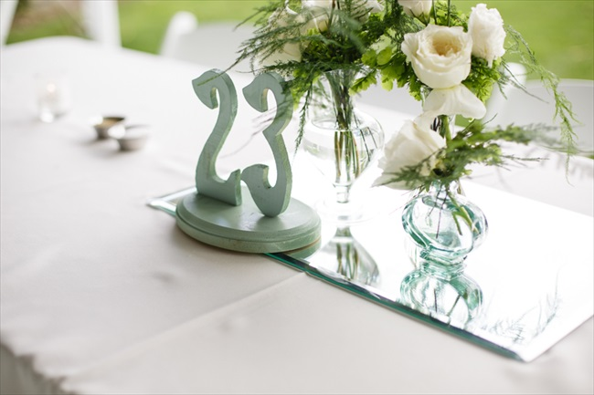 Table number and mirror with vase of flowers for centerpiece | Photo: Searching for the Light Photography LLC | via http://emmalinebride.com/real-weddings/colorado-chic-wedding-kendall-brian/