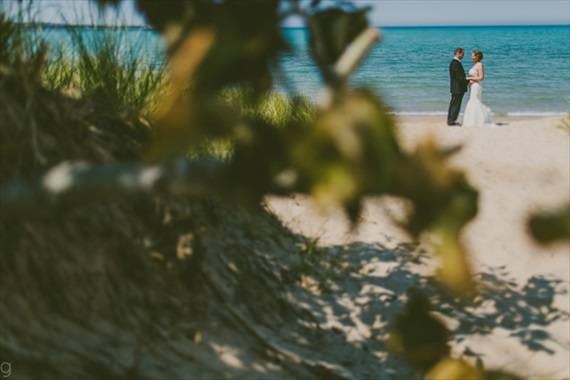 the bride and groom share a moment alone by themselves on a Michigan Beach