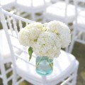 blue mason jars filled with white hydrangea flowers and attached to chairs