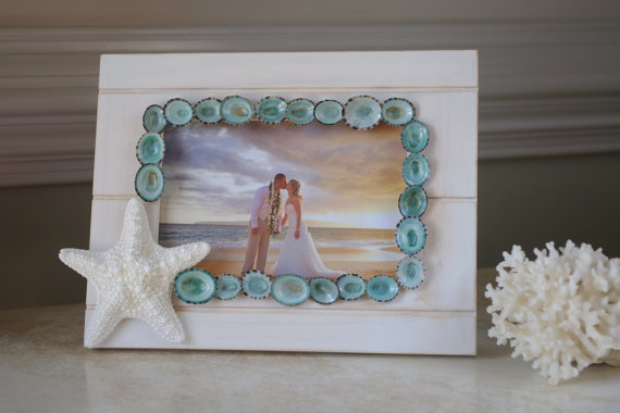 10 Beach Wedding Centerpieces via EmmalineBride.com - limpet shell and starfish frame by By The Seashore