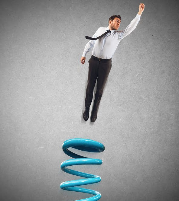 Businessman uses a spring to make leap