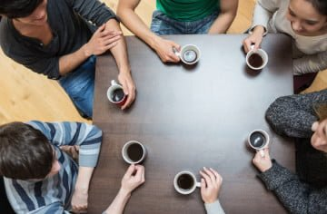 People sitting around table drinking coffee