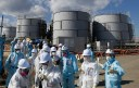 FILE - In this Feb. 10, 2016, file photo, members of a media tour group wearing a protective suit and a mask walk together after they receive a briefing from Tokyo Electric Power Co. employees (in blue) in front of storage tanks for radioactive water at the tsunami-crippled Fukushima Dai-ichi nuclear power plant in Okuma, Fukushima Prefecture, northeastern Japan. In an AP interview, a chief architect of an 妬ce wall� being built into the ground around the broken Fukushima nuclear plant defends the project but acknowledges it won稚 be watertight, and as much as 50 tons of radiated water will still accumulate each day. TEPCO, the utility that operates the facility, resorted to the $312 million frozen barrier after it became clear that something had to be done to stem the flow of water into and out of the broken reactors so that they can be dismantled. (Toru Hanai/Pool Photo via AP, File)