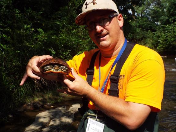 Robert Hughes holding a Red-eared Slider turtle he caught while sampling Solomon Creek