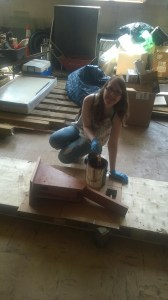 Kaityln White staining up one of EPCAMR's Blue Bird boxes with a manganese oxide wood stain.
