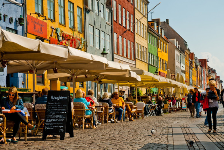 Photo of restaurant patios along Nyhavn in Copenhagen, Denmark.