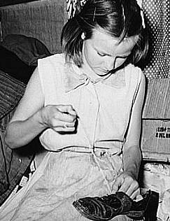 Great Depression: Daughter of white migrants repairing shoes with cotton thread. Sebastian, Texas. Photo by Russell Lee. Courtesy Library of Congress, Prints & Photographs Division, FSA-OWI Collection LC-USF34- 032323-D