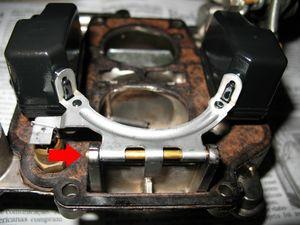 Aqui vamos retirar a bóia. Para isso, use uma ferramenta com ponta bem fina para empurrar, no sentido da seta, a haste que serve de eixo e prende a bóia ao carburador. Quando ela começar a sair, puxe a outra extremidade com um alicate.