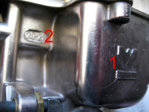 """Lateral do corpo do carburador: Veja a logomarca da Weber (1), e a numeração dos difusores primários (2). No exemplo da foto, os números são """"20"""" e """"21"""", o que significa que o difusor primário (venturi) do primeiro estágio tem 20 mm de diâmetro, e o difusor primário (venturi) do segundo estágio tem 21 mm."""