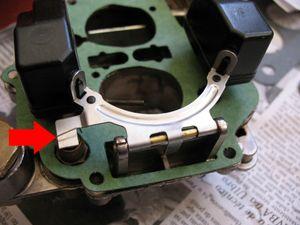 A regulagem da altura da bóia só deverá ser feita caso o carburador esteja dando falta de combustível (nível muito baixo) ou excesso, com possível transbordamento de combustível (nível muito alto). Caso seja necessário regular, faça-o pela lingüeta da haste da bóia que toca a agulha. Com a tampa de cabeça para baixo (como na foto), ao dobrar a lingüeta para cima, você estará aumentando o nível da bóia, e vice-versa. Faça-o com o auxílio de um alicate, para obter maior precisão. Para saber se a altura é certa, coloque um pouco de combustível (ou outro líquido) na cuba, um pouco acima do ponto em que o combustível jorra pelo furo de dentro da câmara injetora. Para manter esse nível, tape o furo com o dedo. Feche o carburador sem parafusá-lo, e sopre pela entrada de combustível, mantendo-o o mais horizontal possível. Se o ar do sopro não entrar, a altura é certa. Caso o ar entre, diminua um pouco o nível da bóia até que isso não ocorra mais. Depois de ajustada, a bóia deverá ficar mais ou menos paralela a tampa do carburador, quando esta estiver de cabeça para baixo, assim como na foto.