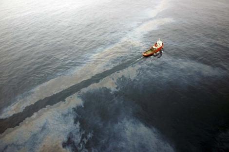 Un barco de salvamento limpia el crudo vertido por la plataforma de Repsol frente al Delta del Ebro.   Foto: Efe