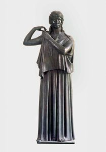 Woman fastening her peplos (Peplophoros). Bronze. Found in the Villa dei Papyri, Herculaneum. MANN 5619. ©The Superintendence for the Archaeological Heritage of Naples (SAHN).