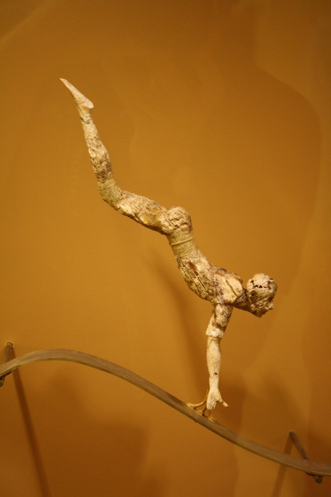 An ivory figurine representating a bull-leaper from a three dimensional composition (with two other figures and a bull) depicting this Minoan sporting or religious activity. Hair would have been added using bronze wire and clothes in gold leaf, 1600-1500 BCE. It is perhaps the earliest known attempt in sculpture to capture free movement in space. (Archaeological Museum Herakleion)