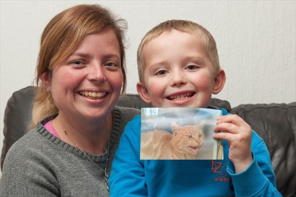 猫の写真をもつ男の子