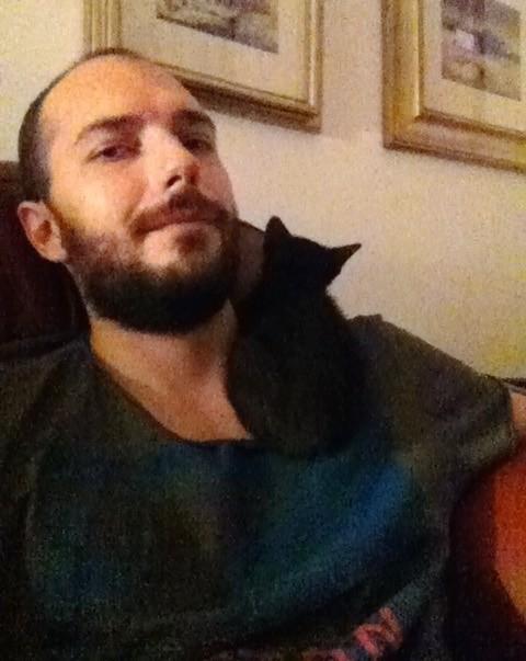 男性に寄り添う黒猫