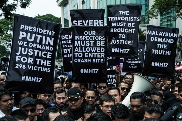 Malaysians hold up banners during a rally outside the Russian embassy in Kuala Lumpur on July 22, 2014. © AFP