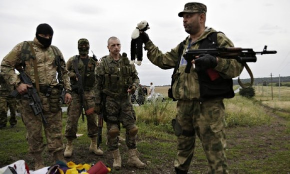 A pro-Russia fighter holds up a toy found among the debris at the crash site of MH17. Photograph: Dmitry Lovetsky/AP