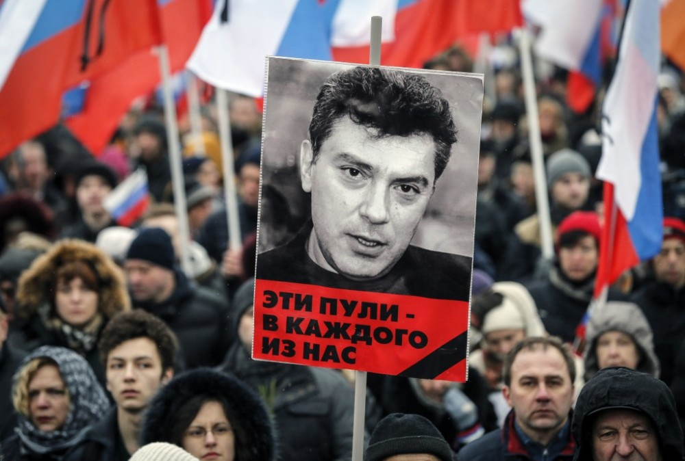 "Boris Nemtsov Memorial March. The sign says in Russian: ""These bullets hit all of us"""