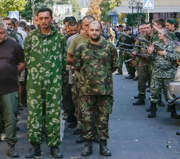 Russian forces (R) armed with assault rifles with bayonets escort a column of Ukrainian prisoners of war during a military parade across central Donetsk on August 24, 2014. Parading POWs this way is a violation of the Geneva Convention. (Image: Maxim Shemetov, REUTERS)