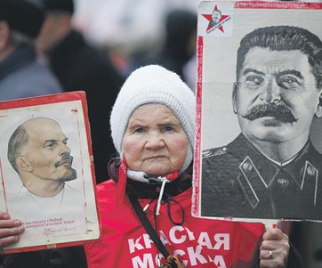 An old Russian woman holding portraits of Lenin and Stalin at a demonstration in Moscow (Image: Reuters)
