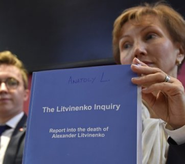 Marina Litvinenko holding the report of the British judicial investigation into the death of her husband Alexander Litvinenko next to their son Anatoly (Image: Reuters)