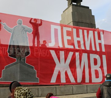 """Lenin Lives!"" sign at a demonstration of the left in Yekaterinburg, Russia next to the city's main Lenin statue. 22 April 2016 года (Image: social media)"