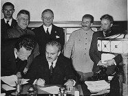 Beaming Stalin supervising the signing of the so-called Molotov-Ribbentrop Pact dividing Poland between Hitler's regime and his own, Aug 23, 1939. From left to right: Richard Schulze-Kossens, Waffen-SS officer; Boris Shaposhnikov, Chief of the General Staff of the Red Army; Alexey Shkvarzev, Soviet Ambassador in Germany; Joachim von Ribbentrop, German Minister of Foreign Affairs; Vyacheslav Molotov, Soviet Minister of Foreign Affairs (sitting); Joseph Stalin, Soviet dictator; Vladimir Pavlov, First Secretary of the Soviet embassy in Germany (Image: TASS)