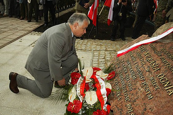 Ex-president of Poland Lech Kaczynski kneels before the monument to Jozef Kuras.