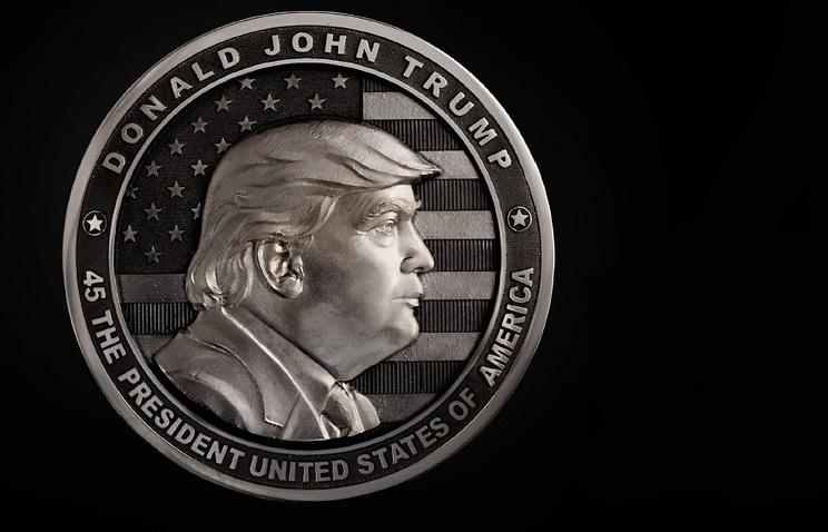 "A two-pound coin dedicated to Donald Trump created in Russia for his inauguration. The back of the coins shows the Statue of Liberty against a background of the American flag with inscription reading, ""In Trump We trust."" (Image: Art Grani)"