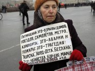 "A woman at the 2015 Boris Nemtsov Memory March on 1 March 2015 in Moscow, Russia. Her sign says: ""Putinism it is explosions of apartment buildings, airplanes, metro stations, airports; it is incidents and fires; it is tragedies of 'Kursk,' 'Nord-Ost,' Beslan; it is murders, corruption, mafia, war..."" (Image: kykyryzo.ru)"