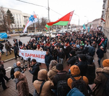 Participants of the protest march under two flags - the official green-red one and the red-white one associated with the opposition. Photo: tut.by