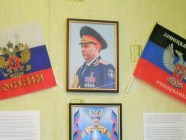 "Flags of Russia and the ""Donetsk People's Republic"" next to the portrait of Aleksandr Zakharchenko, its Kremlin-appointed ""leader,"" on a school wall in the frontline city of Horlivka, occupied Donbas"