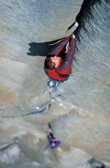man rock climbs a crack on the headwall of The Salathe Wall on El Capitan in Yosemite National Park, California.