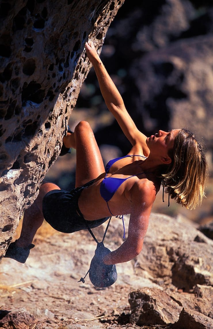 woman rock climbing / bouldering at The Happy Boulders near Bishop, California