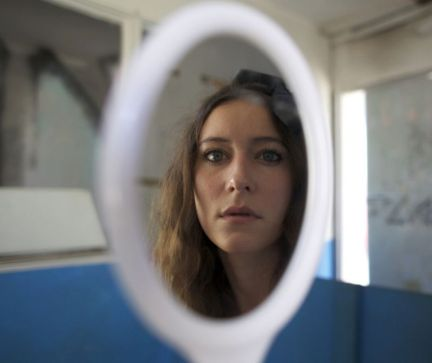 Depressed woman looking into mirror